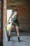 Girl near the brick wall in military style. Stock Image