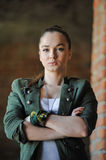 Girl near the brick wall in military style. Royalty Free Stock Photography