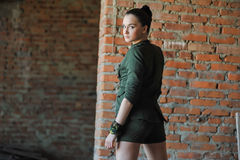 Girl near the brick wall in military style. Stock Photos