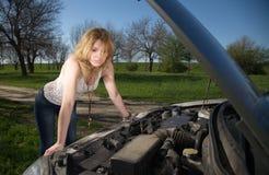 Girl near the car with an open hood. Stock Photos