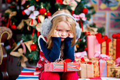 The girl near a Christmas fir-tree in red tones Stock Image