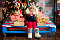 The girl near a Christmas fir-tree in red tones Royalty Free Stock Photo