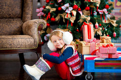 The girl near a Christmas fir-tree in red tones Royalty Free Stock Photos