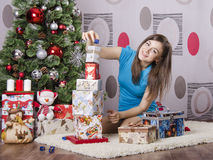 Girl near a Christmas tree collects from gifts pyramid Royalty Free Stock Photos