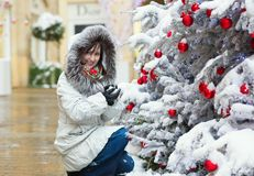 Girl near Christmas tree covered with snow Royalty Free Stock Image