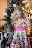 The girl near a Christmas tree with a favorite toy rabbit, boxes, Christmas, New Year, lifestyle, holiday, vacation, waiting for s Stock Photos