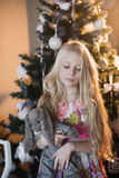 The girl near a Christmas tree with a favorite toy rabbit, boxes, Christmas, New Year, lifestyle, holiday, vacation, waiting for s Royalty Free Stock Photo