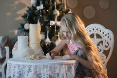 The girl near a Christmas tree with a favorite toy rabbit writes a letter to Santa, boxes, Christmas, New Year, lifestyle, holiday Stock Image