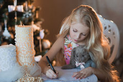 The girl near a Christmas tree with a favorite toy rabbit writes a letter to Santa, boxes, Christmas, New Year, lifestyle, holiday Stock Images