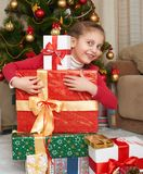 Girl near christmas tree and gift boxes, happy holiday and winter celebration, dressed in red Stock Image