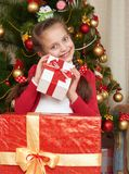 Girl near christmas tree and gift boxes, happy holiday and winter celebration, dressed in red Stock Photography