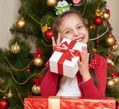 Girl near christmas tree and gift boxes, happy holiday and winter celebration, dressed in red Stock Photo