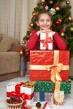 Girl near christmas tree and gift boxes, happy holiday and winter celebration, dressed in red Stock Images