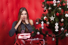 Girl near the Christmas tree with gifts. On red background Royalty Free Stock Photos