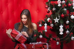 Girl near the Christmas tree with gifts. On red background Stock Images