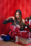 Girl near the Christmas tree with gifts. On red background Royalty Free Stock Photo