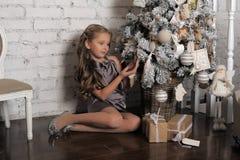 Girl near the Christmas tree Royalty Free Stock Image