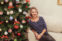 Girl near the Christmas tree in a house interior Royalty Free Stock Image