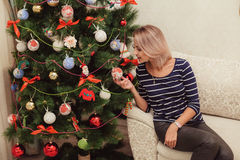 Girl near the Christmas tree in a house interior Stock Image