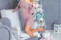 Girl near the Christmas tree in a knitted dress cappuccino color royalty free stock photo