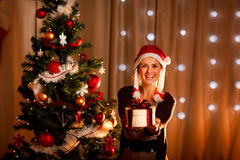 Girl near Christmas tree presenting gift box Stock Images