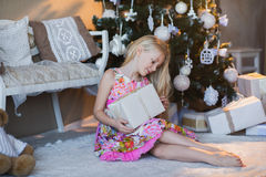 Girl near Christmas tree with presents and toys, boxes, Christmas, New Year, lifestyle, holiday, vacation, waiting for santa. Blond girl in a beautiful dress Stock Image