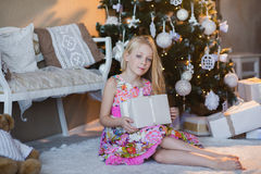 Girl near Christmas tree with presents and toys, boxes, Christmas, New Year, lifestyle, holiday, vacation, waiting for santa. Blond girl in a beautiful dress Stock Photography