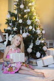 Girl near Christmas tree with presents and toys, boxes, Christmas, New Year, lifestyle, holiday, vacation, waiting for santa Royalty Free Stock Photography