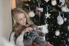 Girl near Christmas tree with presents and toys, boxes, Christmas, New Year, lifestyle, holiday, vacation, waiting for santa. Blond girl in a beautiful dress Royalty Free Stock Photography