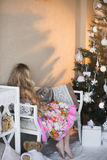 Girl near Christmas tree with presents and toys, boxes, Christmas, New Year, lifestyle, holiday, vacation, waiting for santa. Blond girl in a beautiful dress stock photo