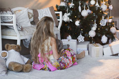 Girl near Christmas tree with presents and toys, boxes, Christmas, New Year, lifestyle, holiday, vacation, waiting for santa Stock Photo