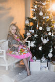 Girl near Christmas tree with presents and toys, boxes, Christmas, New Year, lifestyle, holiday, vacation, waiting for santa. Blond girl in a beautiful dress Royalty Free Stock Images