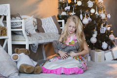 Girl near Christmas tree with presents and toys, boxes, Christmas, New Year, lifestyle, holiday, vacation, waiting for santa. Blond girl in a beautiful dress Stock Images