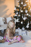 Girl near Christmas tree with presents and toys, boxes, Christmas, New Year, lifestyle, holiday, vacation, waiting for santa Stock Images