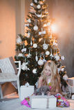 Girl near Christmas tree with presents and toys, boxes, Christmas, New Year, lifestyle, holiday, vacation, waiting for santa. Blond girl in a beautiful dress Royalty Free Stock Photo