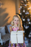 Girl near Christmas tree with presents and toys, boxes, Christmas, New Year, lifestyle, holiday, vacation, waiting for santa. Blond girl in a beautiful dress Royalty Free Stock Photos