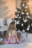 Girl near Christmas tree with presents and toys, boxes, Christmas, New Year, lifestyle, holiday, vacation, waiting for santa. Blond girl in a beautiful dress Stock Photos