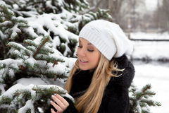 Girl near the Christmas tree in snow Stock Photos