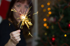 The girl near a Christmas tree with sparkler. Stock Images