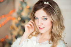 Girl near the decorated Christmas tree in beautiful light interior Stock Images