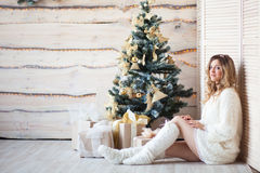 Girl near the decorated Christmas tree in beautiful light interior Stock Photo
