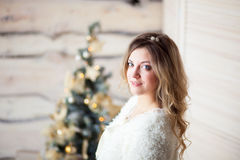 Girl near the decorated Christmas tree in beautiful light interior Stock Photos
