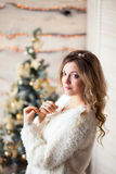 Girl near the decorated Christmas tree in beautiful light interior Royalty Free Stock Images