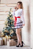 Girl near the decorated Christmas tree in beautiful light interior Royalty Free Stock Image
