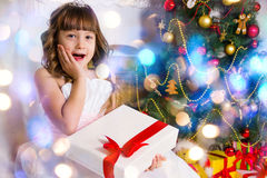 Girl near the decorated Christmas tree, holds a white Royalty Free Stock Image