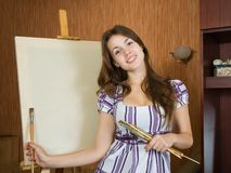 Girl near easel in interior Royalty Free Stock Photos