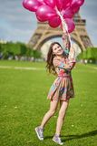 Girl near the Eiffel tower in Paris with huge bunch of pink balloons stock photo