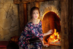 The girl near a fireplace Royalty Free Stock Image