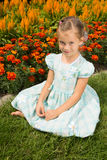 Girl Near Flowerbed. Young girl sits next to beautiful flowerbed in a summer park Stock Photo
