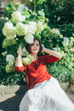 Girl near the flowers of hydrangea Stock Photo